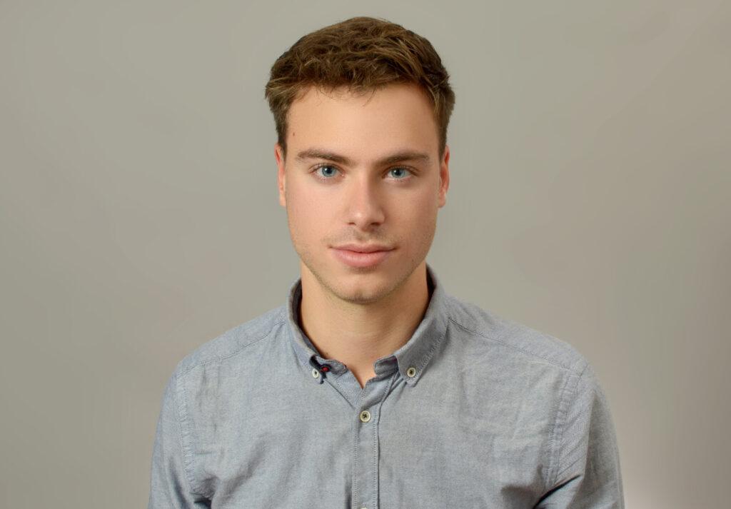 Aris Kress schaut frontal in die Kamera, er trägt ein graues Hemd.