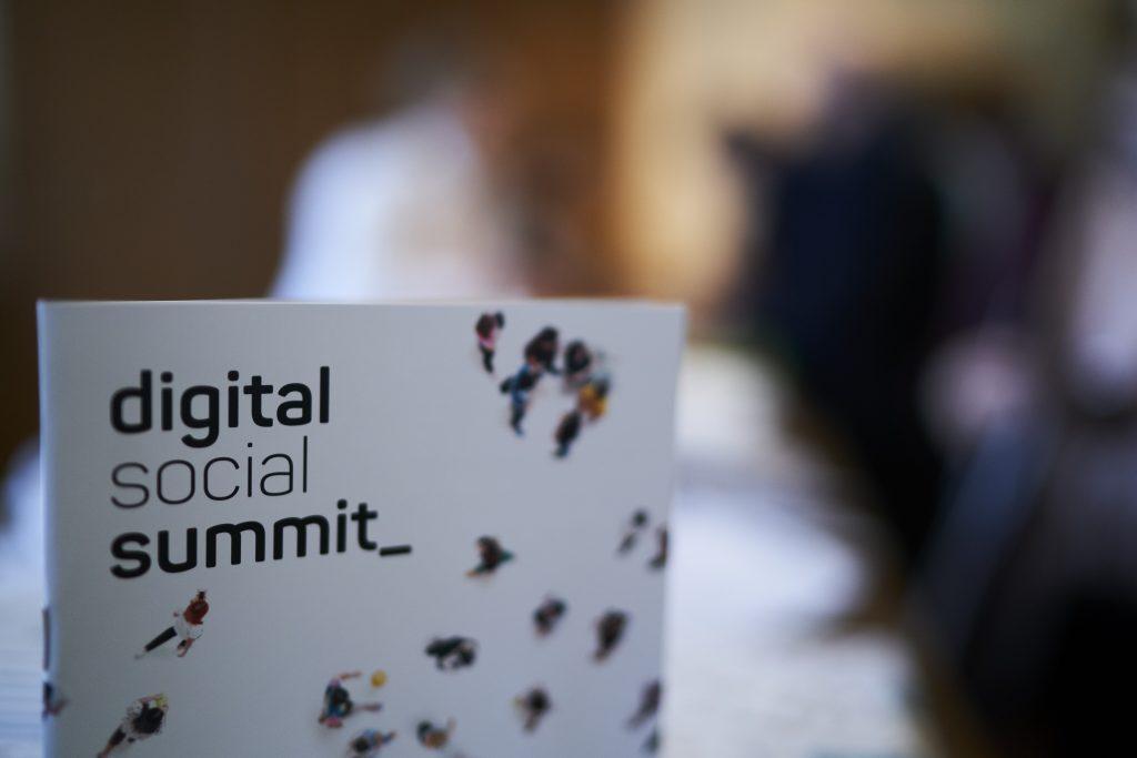 Ein Programmheft des Digital Social Summit mit verschwommenem Hintergrund.