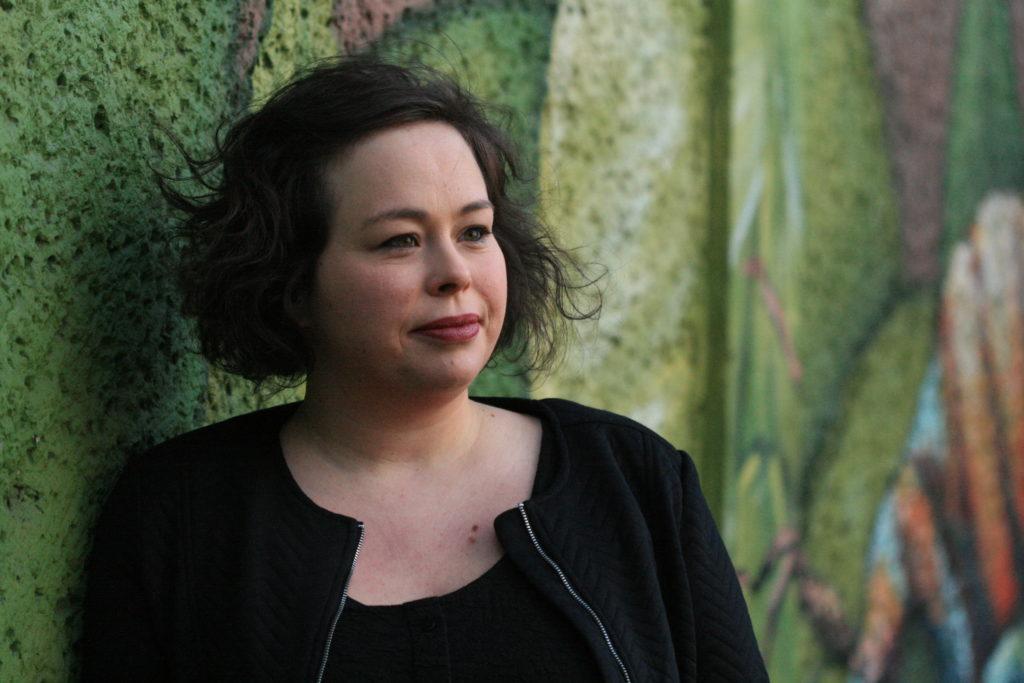 Bild zeigt D3 Redakteurin Friederike Petersen vor einer grünen Wand.