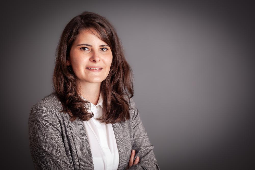 Teresa Staiger, BBE in weisser Bluse und grauer Strickjacke vor einem grauen Hintergrund