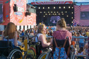Zwei Rollstuhlfahrerinnen auf einem Festival.