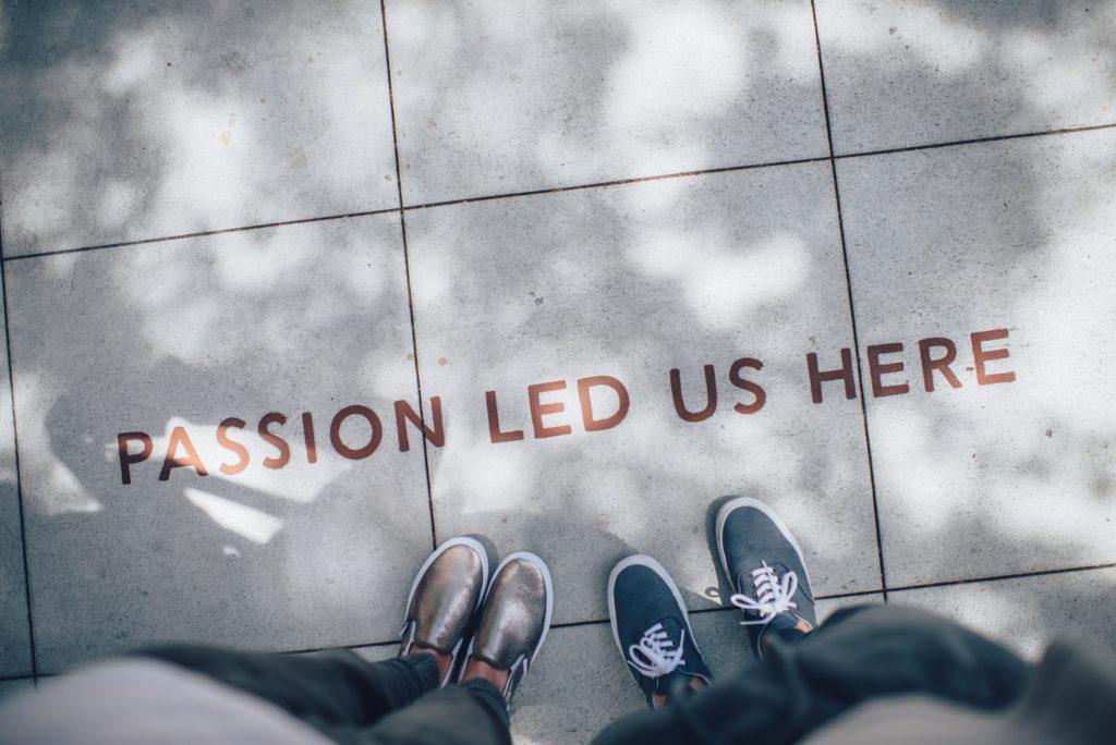 """Zwei Beinpaare stehen auf einer Straße. Dort steht """"Passion led us here""""."""