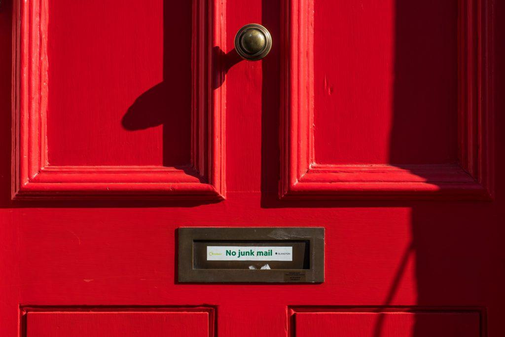 """Eine rote Tür mit einem Briefschlitz. Auf dem steht """"No junk mail""""."""