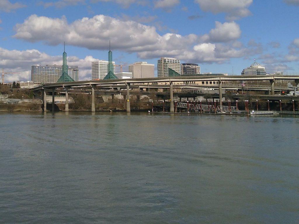 Blick über einen Fluss auf das Kongresszentrum in Portland, Oregon. Hinter einer Brücke ist das Messegelände mit zwei grünen Türmen zu sehen.