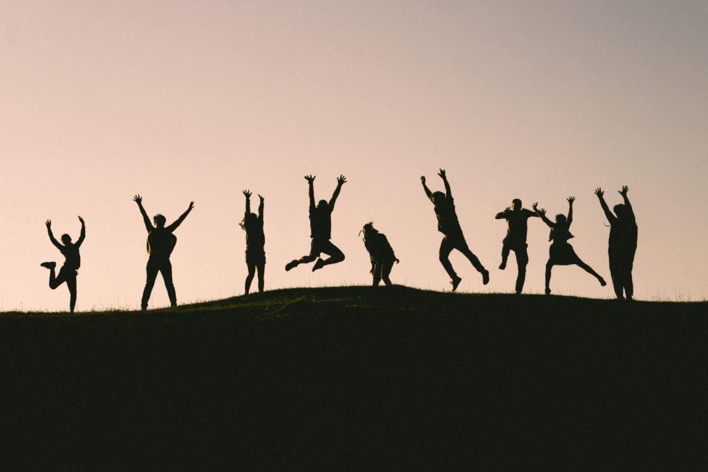 9 Menschen springen auf einer Wiese.