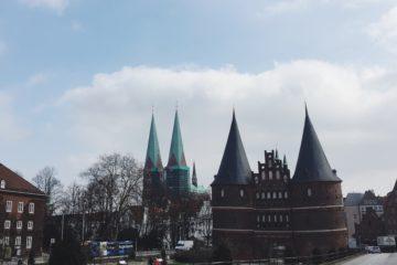 Das Lübecker Holstentor im Sonnenschein. Zu sehen sind die beiden Türme des Tors und die zwei Türme des Lübecker Doms.