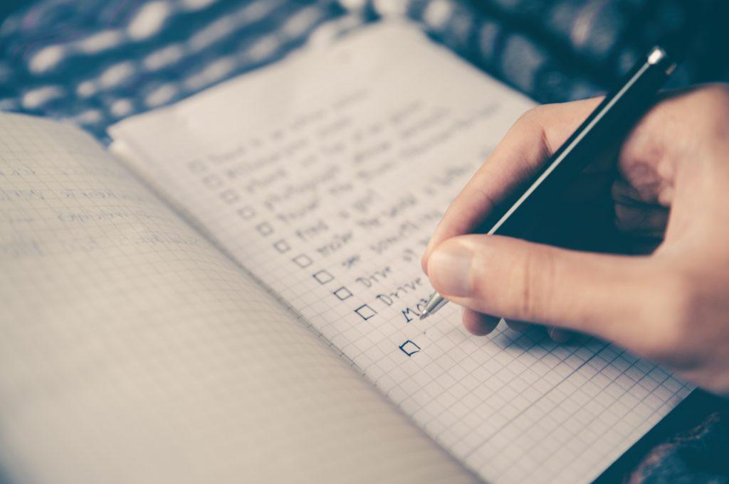 Eine Hand schreibt in ein Notizbuch.