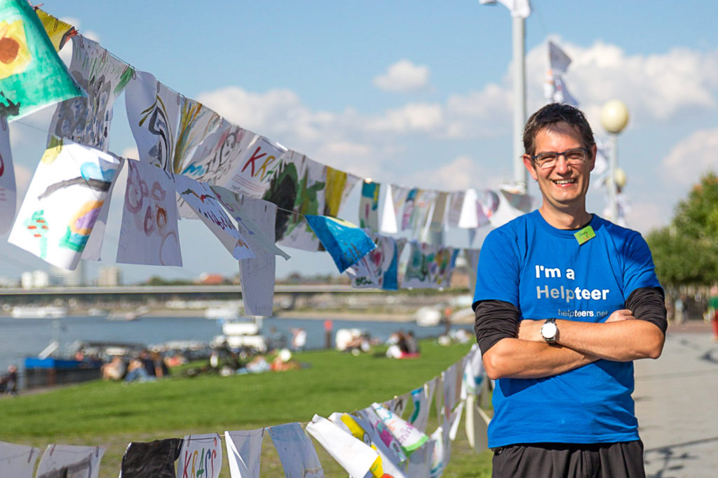 Georg Staebner steht draußen vor einer großen Wäscheleine, die mit selbstgemalten Kinderbildern behängt ist.
