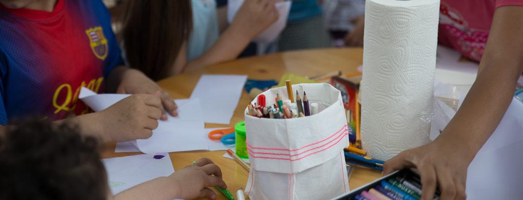 Ein Tisch mit Stiften und malenden Kinderhänden.