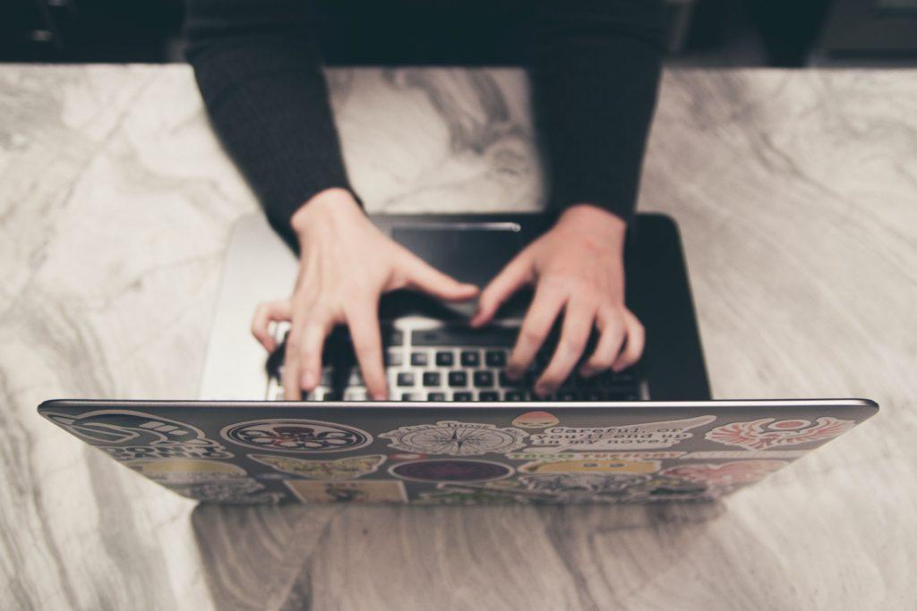 Man sieht von oben auf einen laptop, zwei hände liegen auf der Tastatur.