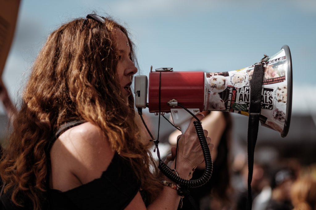 Eine Frau spricht in ein Megafon.