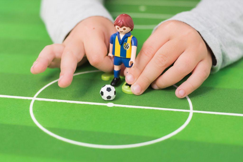 Eine Playmobilfigut schießt einen Fußball.
