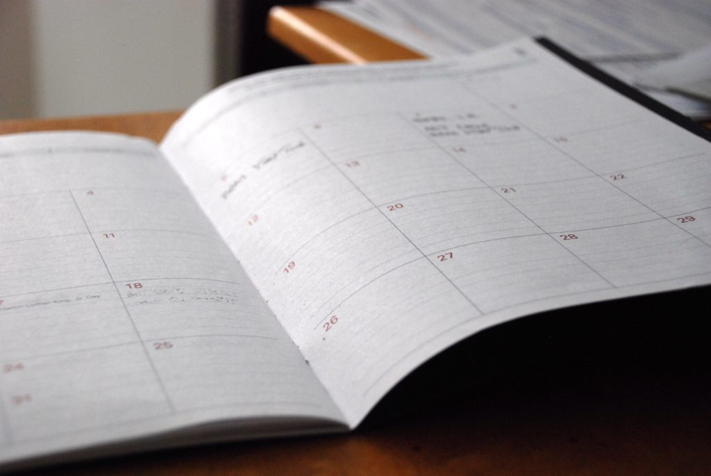 Ein aufgeschlagener Kalender liegt auf einer Tischplatte.