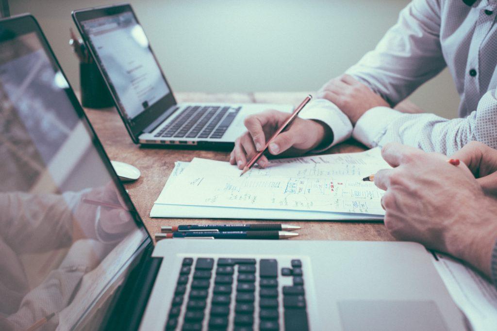Zwei Menschen sitzen gemeinsam an einem Tisch und lernen.