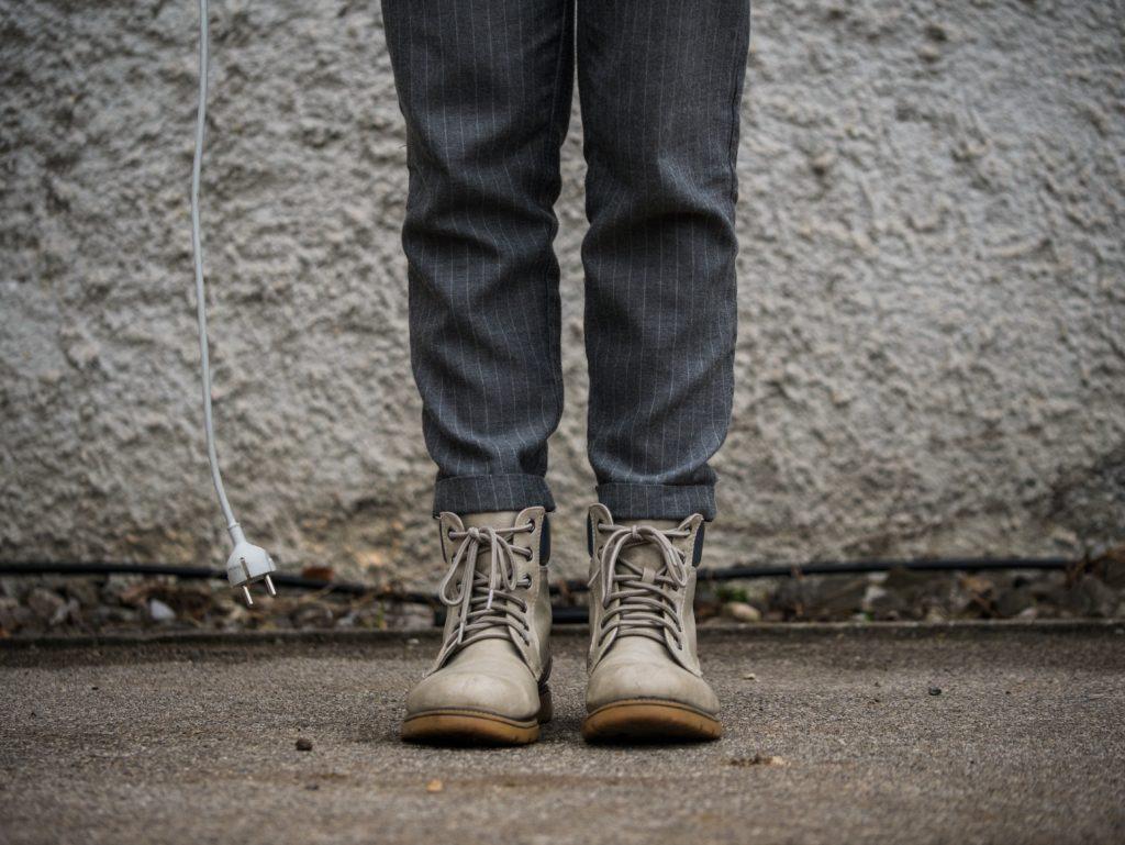 Ein Mensch steht vor einer Wand und hält ein Kabel in der Hand.