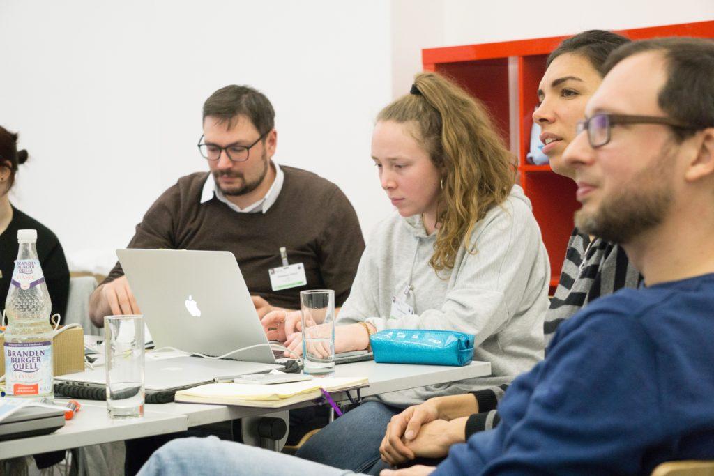 4 junge Menschen sitzen an einem Tisch und arbeiten an zwei Laptops im Rahmen einer Nachtschicht in Berlin.
