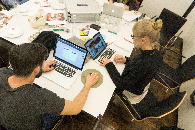 Man sieht zwei junge Menschen die mit Laptops über Eck an einem Schreibtisch sitzen und für ein Projekt der Nachtschicht arbeiten.