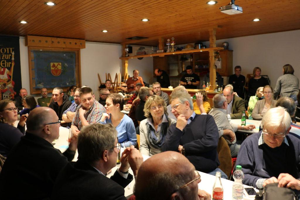 Ein voller Dorfsaal im Ort Bremke. Viele Menschen sitzen an langen Tischen.