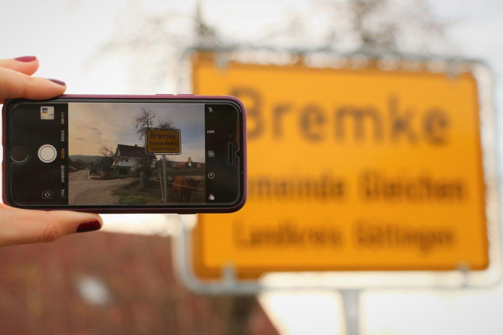 Man sieht ein Smartphone, das im Foto-Modus vor das Ortsschild des Ortes Bremke gehalten wird.