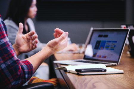 Man sieht die Hände eines Menschen, der an einem Besprechungstisch gestikuliert. Vor ihm liegen ein Notizbuch, ein Handy und ein Laptop.