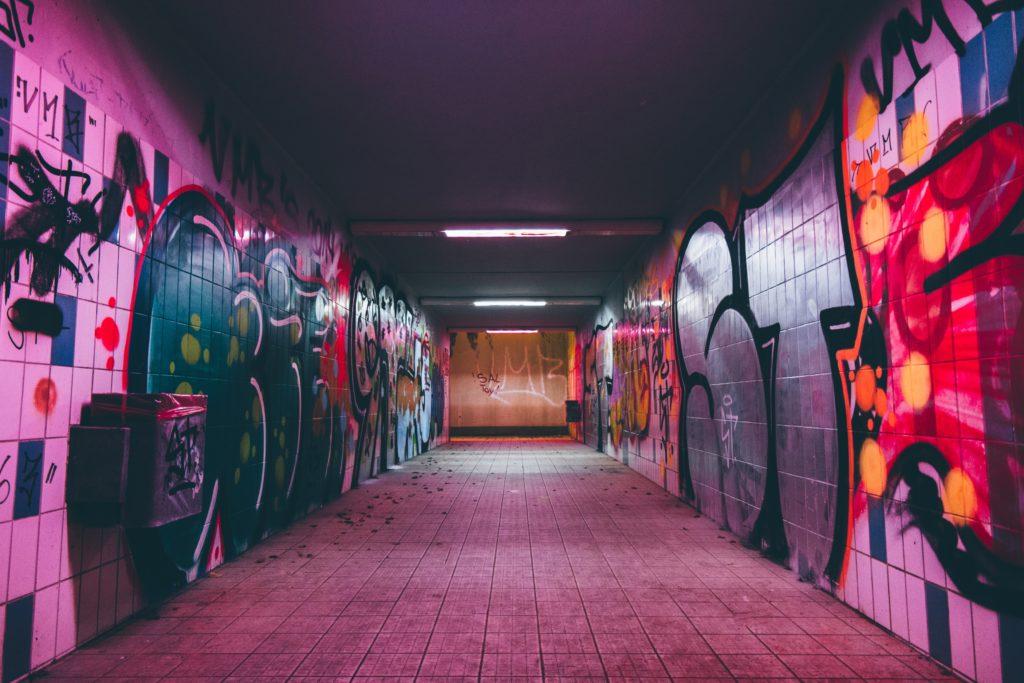 Das Foto zeigt eine mit Grafitti besprühte und von Neonröhren beleuchtete Fußgängerunterführung.