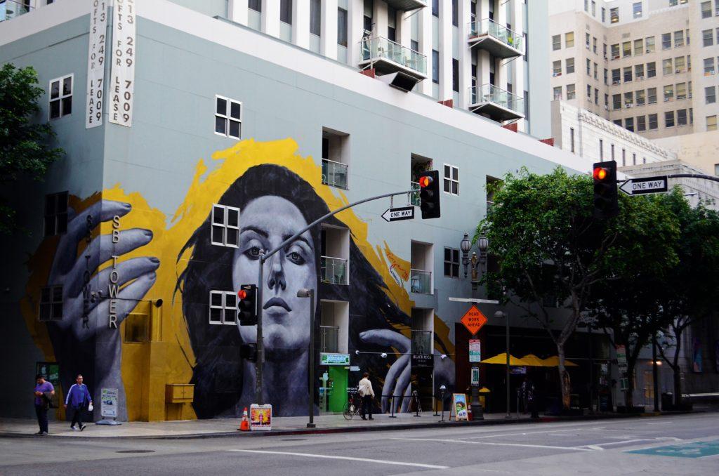 Das Foto zeigt eine Straßenkreuzung mit einem Haus, auf das das Bild einer Frau gesprüht wurde, die von gelbem Schein umgeben ist.