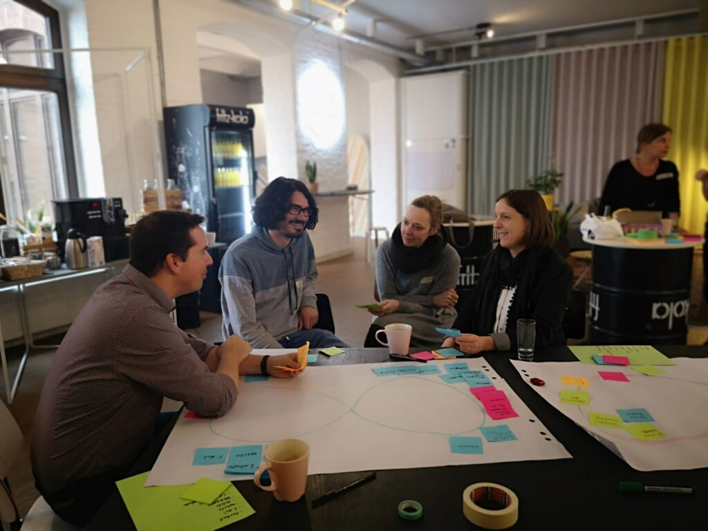 Eine Grupppe junger Menschen sitzt beim D3 Workshop in der Blogfabrik Kreuzberg an einem großen Tisch, auf dem Post-Its und Stifte auf einem Flipchartpapier liegen. Im Hintrgrund erkennt man einen Bar-Kühlschrank und Vorhänge der Blogfabrik Kreuzberg.