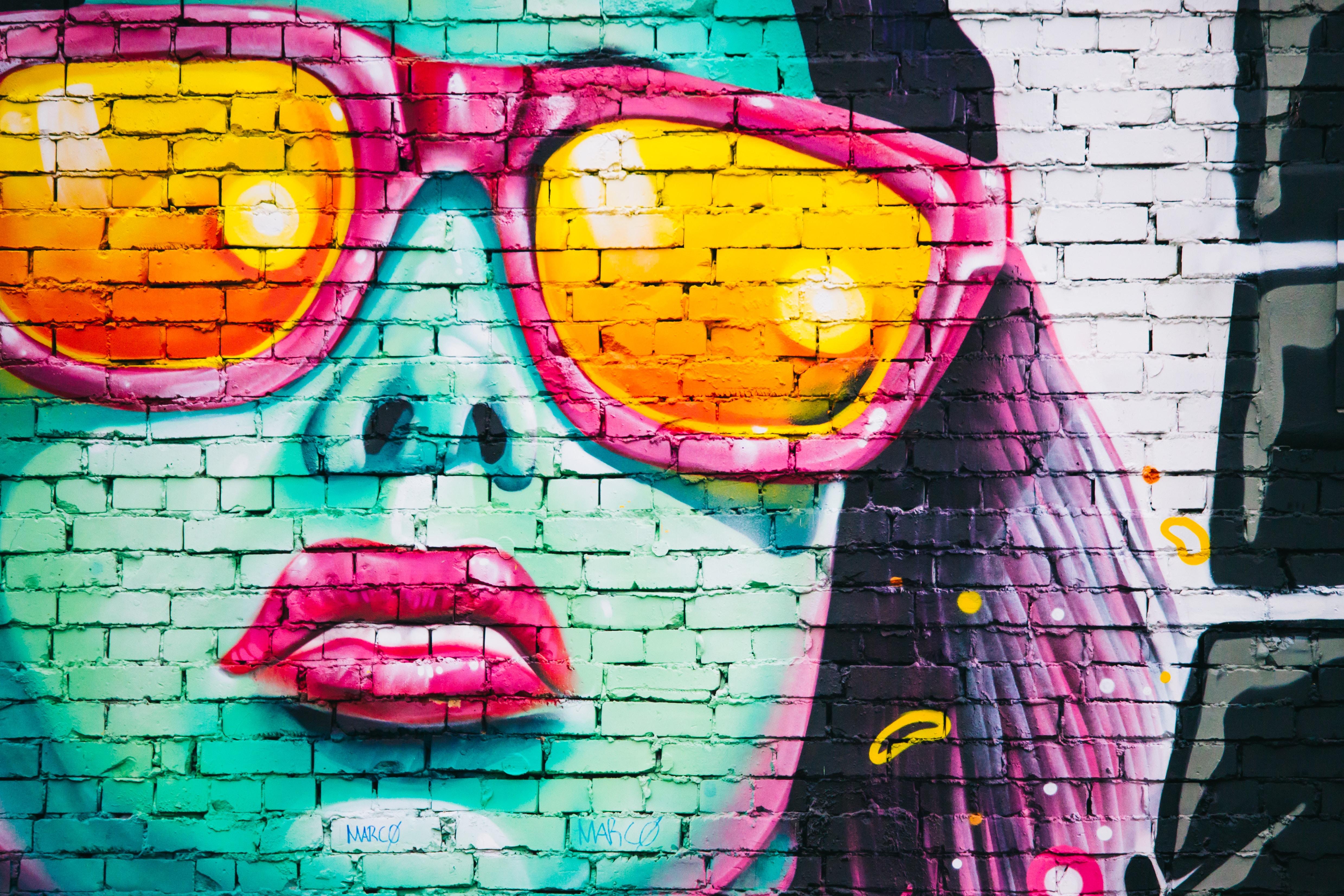 Graffiti auf einer weissen Mauer zeigt eine Nahaufnahme einer Frau in Neonfarben