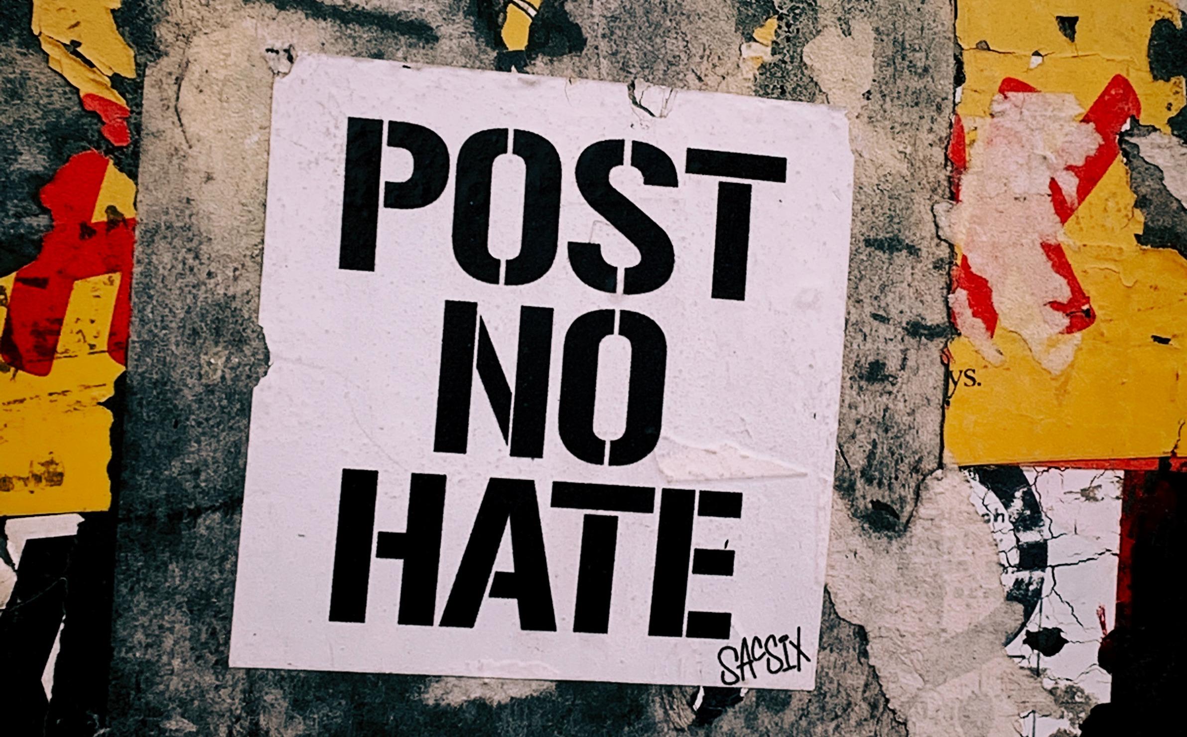 Auf einer stark abgenutzten Außenwand klebt ein Plakat in großen schwarzen Buchstaben auf weissem Grund auf dem steht: Post no hate.