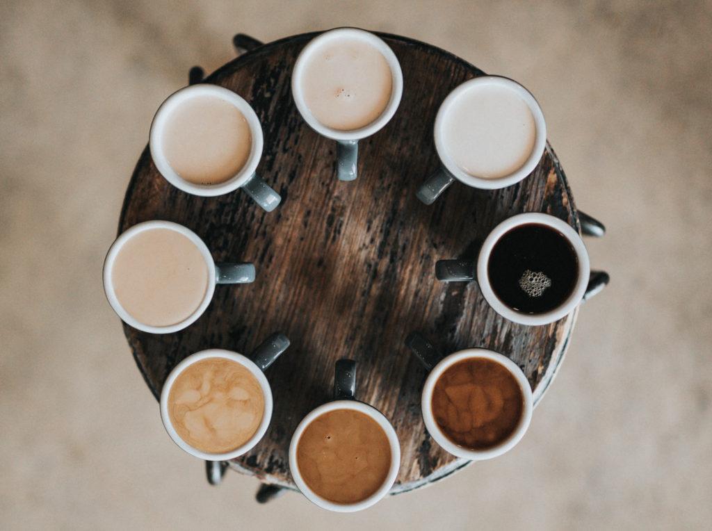 Ein runder Holztisch von oben otografiert. Auf ihm stehen 9 volle Kaffeebecher mit verschiedenen Kaffeesorten.