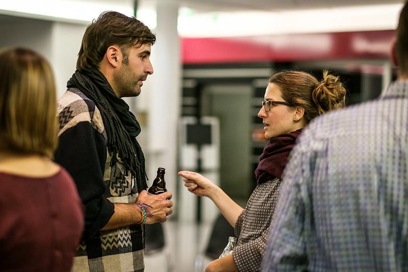 Man sieht zwischen verschwommenen Rücken zwei Menschen ins Gespräch vertieft, der Mann hält ein Bier in der Hand, die Frau gestikuliert.