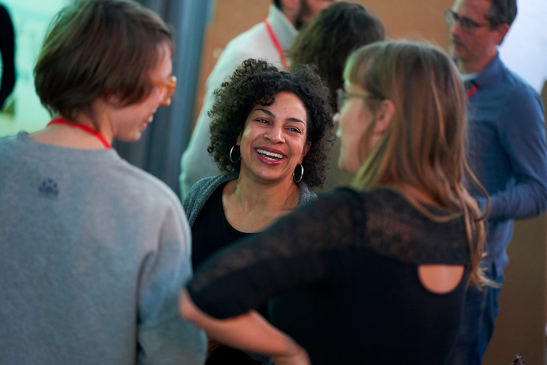 Drei Frauen unterhalten sich, eine junge Frau mit schwarzem Locken schaut lachend in die Kamera, die anderen beiden sind von hinten zu sehen.