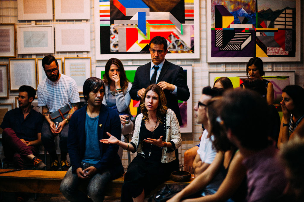 Eine Gruppe Menschen sitzt im Halbkreis, eine Frau gestikuliert.