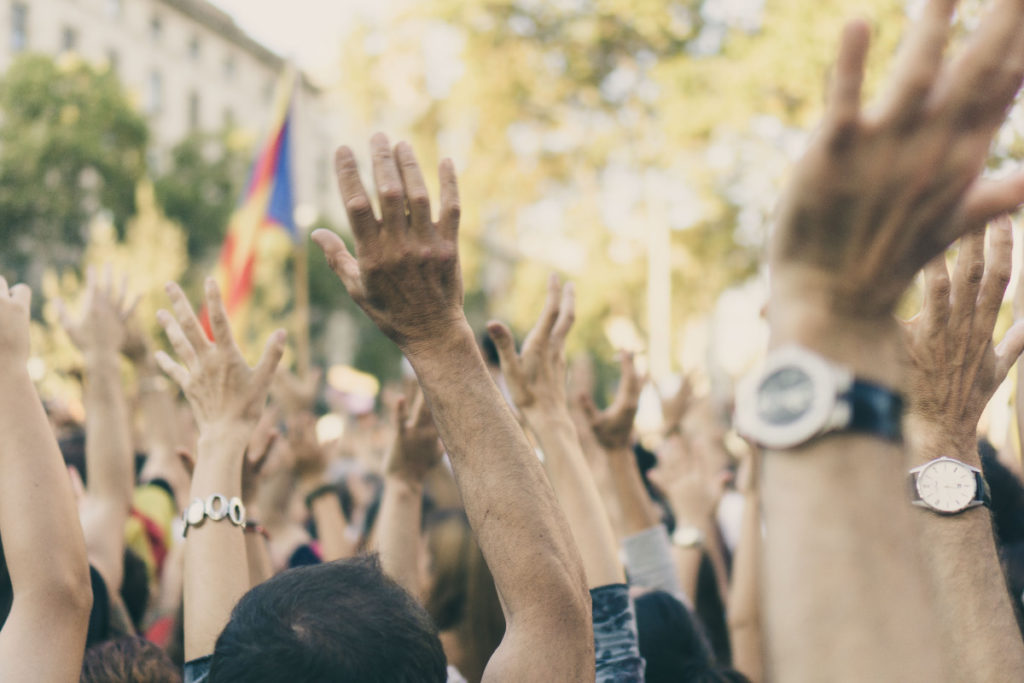 Man sieht über 50 Hände die sich melden. Die dazugehörigen Menschen stehen an einem sonnigen Tag draußen.