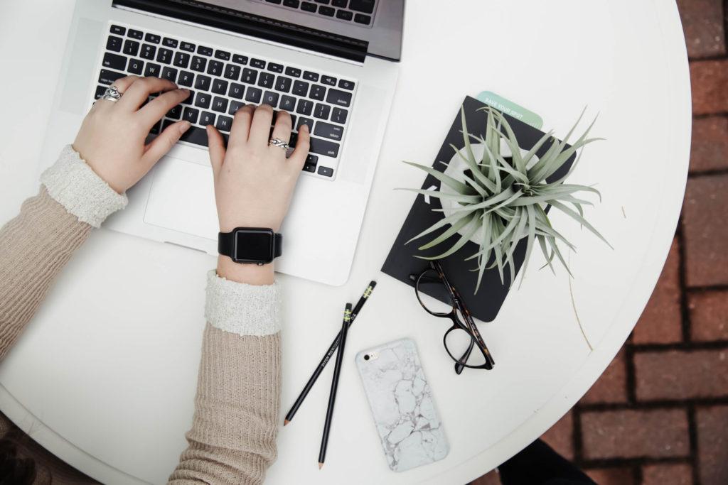 Man sieht von oben auf die Arme und Hände einer Person, die am Laptop arbeitet. Sie sitzt an einem weissen, runden Tisch - neben sich ein Smartphone, Stifte, eine Brille und eine Pflanze. Am Arm trägt sie eine SmartWatch.
