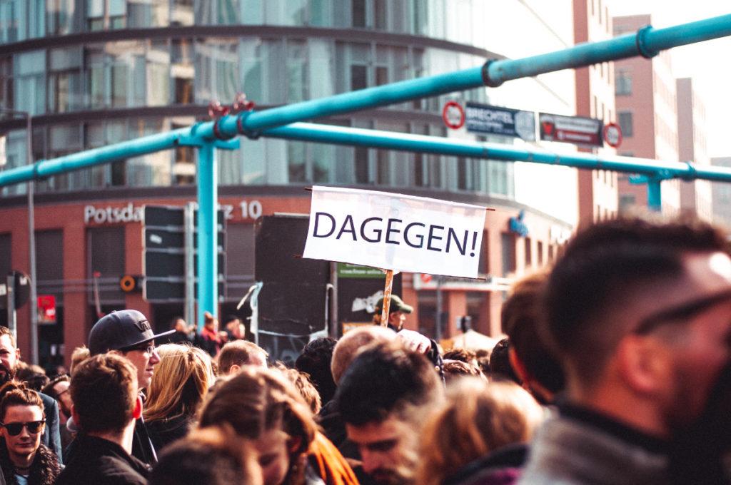 """Man sieht den Ausschnitt einer Demonstration mit vielen Menschen. einer hält in der Bildmitte ein großes weisses Transparent mit der Aufschrift """"Dagegen"""" hoch."""