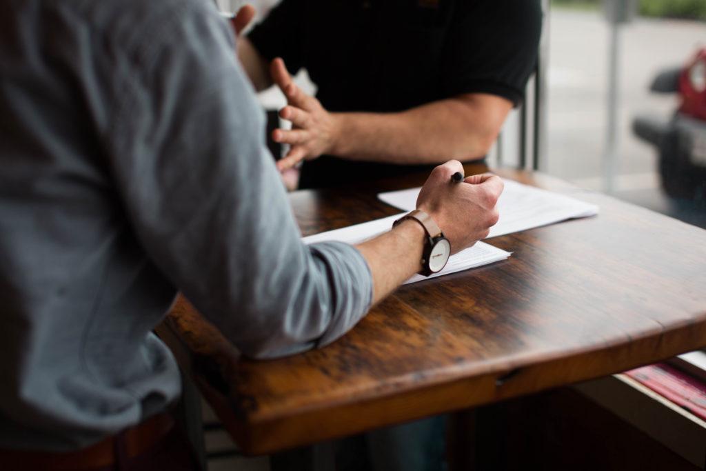 Das Bild zeigt einen Tisch, an dem man die Oberkörper zweier Menschen sitzend sieht. Mit ihren Armen gestikulieren sie.