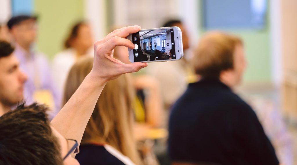 Frau fotografiert die Bühne auf dem D3-Community-Event mit ihrem Smartphone