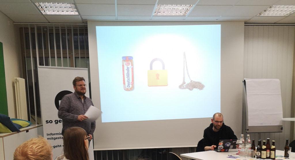 Zwei Männer sind vor einer Leinwand zu sehen, einer hält einen Vortrag. Auf der Leinwand sieht man ein Glas Deutschländer-Würstchen, ein Sicherheitsschloss und ein Fischernetz.