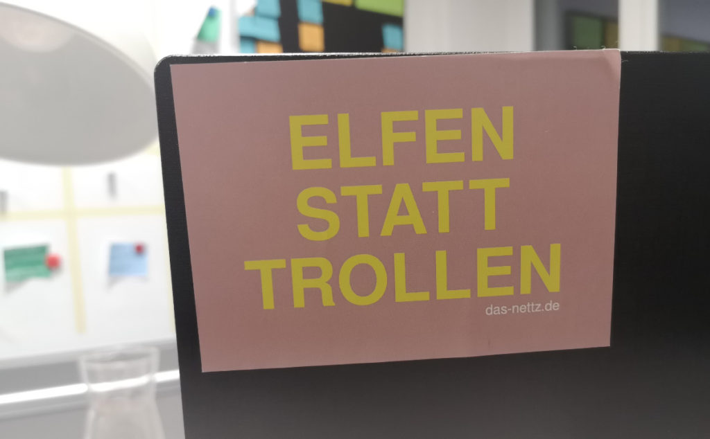 """Man siehr den Aufkleber von """"Das NETTZ"""" auf einem Bildschirm kleben. In gelber Schrift auf rosa steht dort """"Elfen statt trollen""""."""