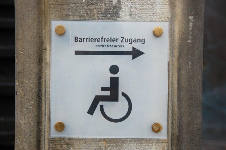 """Schild auf dem ein Menschen mit Rollstuhl sowie der Text """"Barrierefreier Zugang"""" zu sehen ist"""