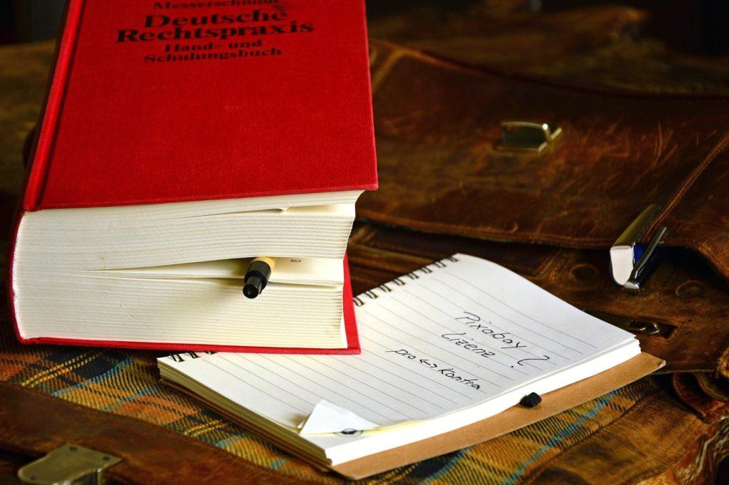 """Buch """"Deutsche Rechtsprechung"""" liegt auf einem Tisch. Davor ein Schreibblock mit dem Text """"Pixabay Lizens?"""""""