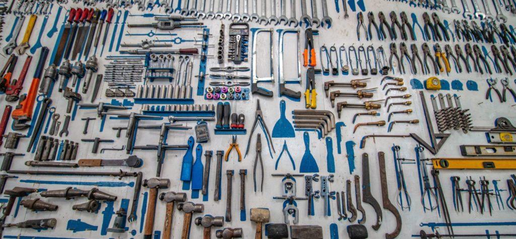 Viele klassische Werkzeuge wie Hammer, Sägen und Schraubenschlüssel liegen auf einer Anrichte.