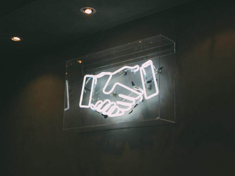 Leuchtbildreklame mit weissen Neonröhren symbolisieren einen Handschlag