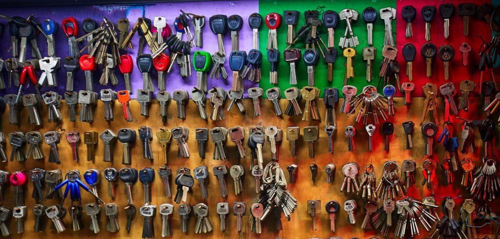 Viele Schlüssel, die an einem bunten Klemmbrett hängen.