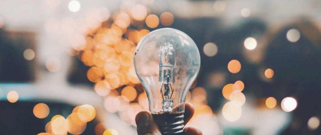 Ein Hand hält eine Glühbirne vor orangenen Lichtpunkten.