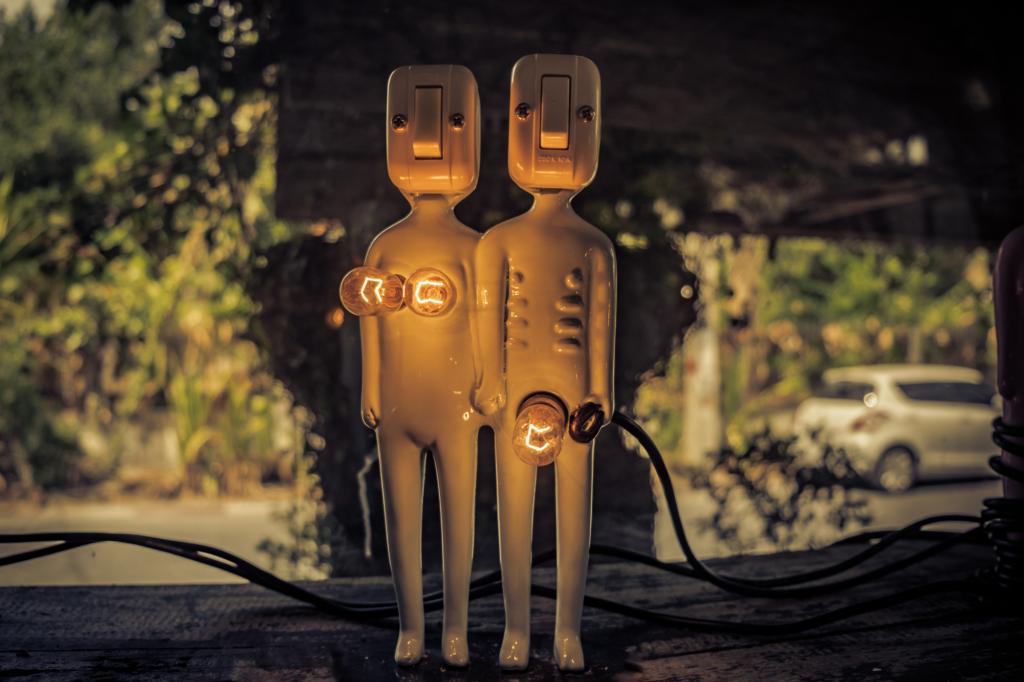 Zwei Plastikfiguren stehen vor einer Straße. Ein Mann, eine Frau. Ihre Geschlechter sind durch Glühbirnen gekennzeichnet.