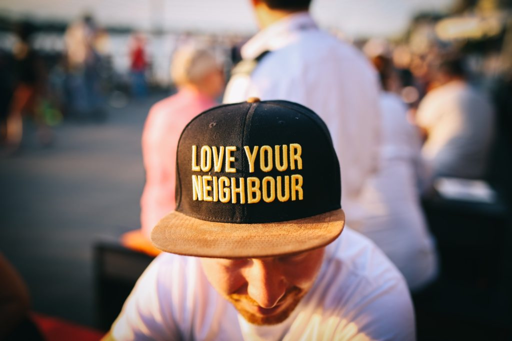 """Mann mit Kappe auf der """"LOVE YOUR NEIGHBOUR"""" steht."""