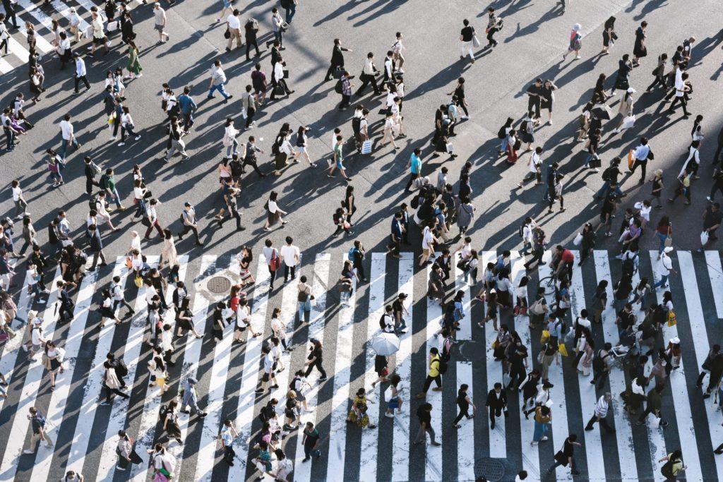 Aufnahme von Menschen, die über einen Zebrastreifen laufen.