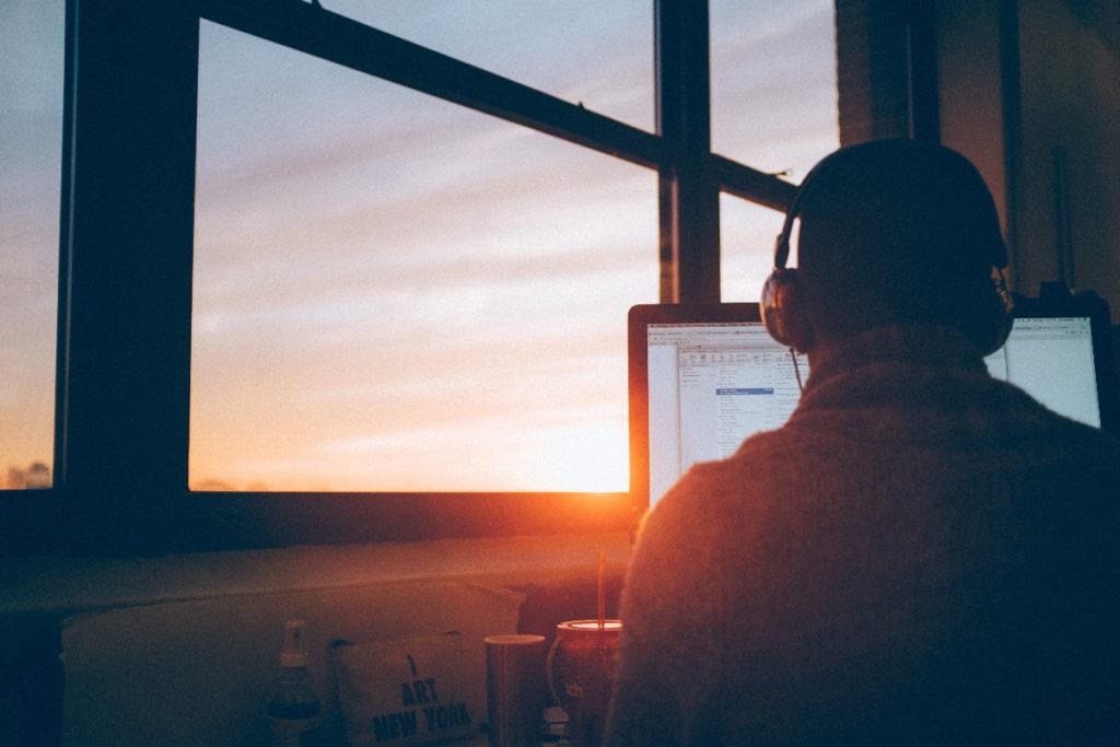 Schräg von hinten wird ein Mann mit Kopfhörern vor einem Bildschirm gezeigt, in der Fensterfront links von ihm geht die Sonne in warmem Licht unter